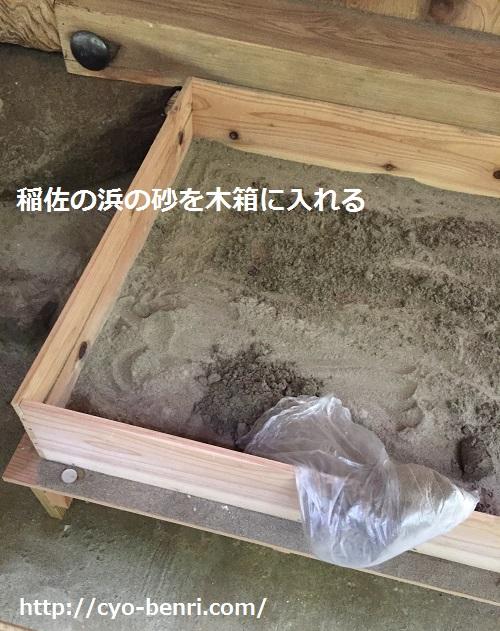 稲佐の浜の砂を木箱に入れる